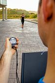 stock photo of chronometer  - Closeup of man trainer hand using a chronometer to timing athletic young woman in a hard training outdoors - JPG