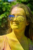 foto of holi  - girl with multicolored face and sunglasses at Holi Festival - JPG