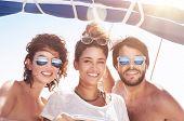 stock photo of mans-best-friend  - Portrait of happy three people having fun on sailboat - JPG
