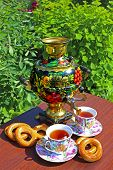 foto of bagel  - Photo Samovar with Khokhloma painting is on the table with cups of tea and bagels - JPG