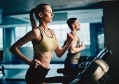 pic of treadmill  - Active young woman and man running on treadmill in gym - JPG