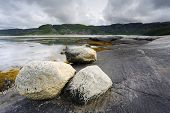 stock photo of fjord  - Rocky coast at an Norwegian fjord with dark clouds - JPG