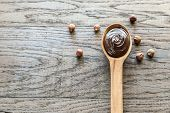 image of chocolate spoon  - Wooden Spoon Of Chocolate Cream With Hazelnuts - JPG