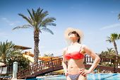 pic of sunbather  - Young woman sunbathing  at the swimming pool - JPG