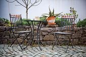 picture of cactus  - Cast iron garden furniture on a patio with a small table and two chairs standing in the sunshine alongside a walled rock garden with a potted cactus on top of the wall - JPG
