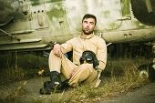 stock photo of helicopters  - Young serious pilot posing near the helicopter - JPG