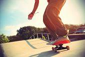 stock photo of skateboard  - skateboarder riding on skateboard at skatepark ramp - JPG