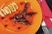 foto of black-cherry  - grilled beef meat with berries fried potatoes and cherry under sweet honey sauce on orange plate over black wooden table - JPG