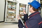 stock photo of fuse-box  - electrician builder engineer inspector checking data of equipment in fuse box - JPG