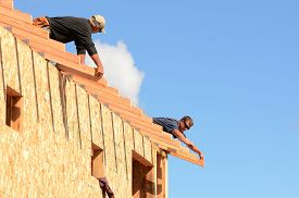 stock photo of rafters  - Layout and installation of roof rafters on a new commercial residential construciton project by framing contactors - JPG