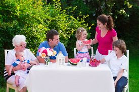 picture of grandparent child  - Big family with children have lunch outdoors - JPG