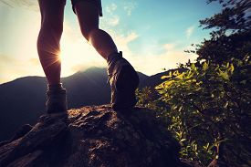 picture of rocking  - woman hiker legs climbing on sunrise mountain peak rock - JPG