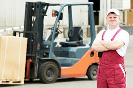 stock photo of forklift  - young warehouse worker portrait in uniform in front of modern storehouse forklift machine - JPG