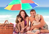 Family Picnicking Under A Sol Umbrella On The Beach