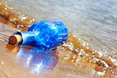 Blue glass bottle on wet sand