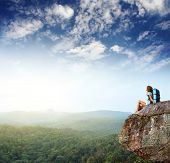 picture of mountain-climber  - Young woman with backpack sitting on cliff and looking to a sky - JPG