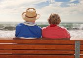 A senior adult couple sitting at a benchand, enjoying their time at the beach.
