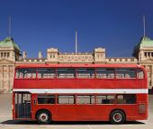 Vintage, red double decker British bus in front of Buckingham Palace, isolated with clipping path