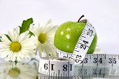 Measurement tape wrapped around green apple/Concept for health, diet