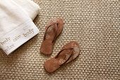 Flip flops with fluffy towels on sea-grass rug poster