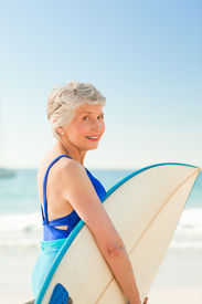 picture of beautiful senior woman  - Woman with her surfboard at the beach