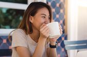 Portrait Of Happy Young Asian Business Woman With Mug In Hands Drinking Coffee In The Morning At Caf poster