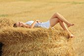 foto of wallow  - Young attractive barefoot girl lying on a bale of yellow straw at field - JPG
