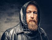 Dramatic Studio Portrait Of Redhead Bearded Male Dressed In A Leather Jacket Over Dark Grey Vignette poster