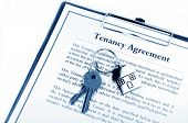 stock photo of rental agreement  - Tenancy agreement and key with symbolic house keyring - JPG