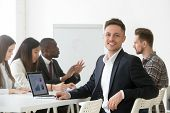 Smiling Young Businessman In Suit Looking At Camera Posing With Laptop At Group Meeting, Happy Proje poster
