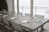 foto of plc  - A grey table with grey chairs and notebooks laying on a table and pens - JPG