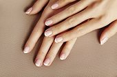 Young Female Palm On Beige Background. Beautiful Glamour Manicure. French Style. Nail Polish. Care A poster