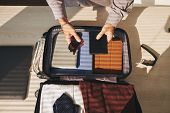 Businessman Preparing For Business Trip.he Is Packing Clothes In Suitcase poster