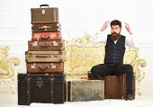 Macho Elegant On Surprised Face Sits Shocked Near Pile Of Vintage Suitcase. Luggage And Relocation C poster
