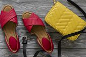 Womens Leather Shoes And Accessories (red Flat Sandals, Yellow Handbag, Black Belt) On Grey Wooden B poster