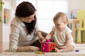 Babysitter Looking After Baby. Child Girl Plays With Sorter Toy Sitting On The Carpet At Home poster
