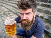 Hipster On Strict Face Drinking Beer Outdoor, Raising Drink Up. Cheers Concept. Man With Beard And M poster