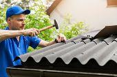 Roofer In Blue Uniform Installing Bitumen Roof Sheets poster
