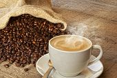 Coffee And Sack Of Coffee Beans - A Cup Of Hot Steaming Coffee On A Rustic Plank Background, With A  poster