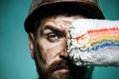 Painter With Painting Roller. Professional Painter Worker In Protective Helmet. Bearded Decorator Ho poster