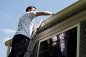 stock photo of clog  - Young man on latter cleaning house gutters - JPG