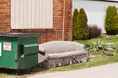 stock photo of dumpster  - Old couch outside beside a trash dumpster - JPG
