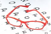 image of snellen chart  - A pair of red reading glasses or spectacles on an Snellen eye chart - JPG