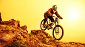 Professional Cyclist Riding the Mountain Bike Down the Rocky Hill. Extreme Sport and Enduro Biking C poster