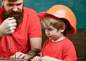 Boy, Child Busy In Protective Helmet Learning To Use Screwdriver With Dad. Father, Parent With Beard poster