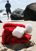 stock photo of santa claus hat  - Father Christmas on Boxing Day relaxing fishing after the busiest night of the year showing his hat clothes and a festive cocktail resting on the rocks and the ocean in the background - JPG
