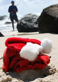 picture of santa claus hat  - Father Christmas on Boxing Day relaxing fishing after the busiest night of the year showing his hat clothes and a festive cocktail resting on the rocks and the ocean in the background - JPG
