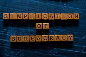 Simplication Of Bureacracy On Wooden Cubes. On Table Background poster