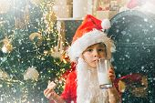 Happy Santa Claus Eating A Cookie And Drinking Glass Of Milk At Home. Portrait Of Santa Claus Drinki poster