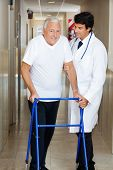stock photo of zimmer frame  - Happy senior man being helped by a male doctor to walk the Zimmer frame - JPG